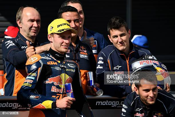 Red Bull KTM Ajo's South African rider Brad Binder poses with his team officers in a celebration to his second fastest time at the parc ferme after...