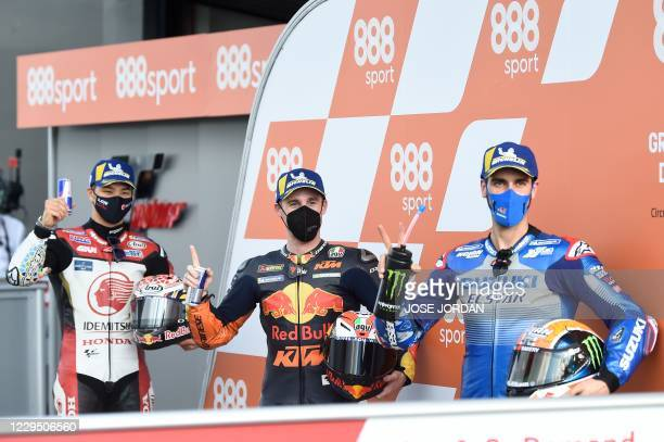 Red Bull KTM Factory Racing's Spanish rider Pol Espargaro , first in the pole, celebrates with Suzuki Ecstar's Spanish rider Alex Rins and LCR Honda...