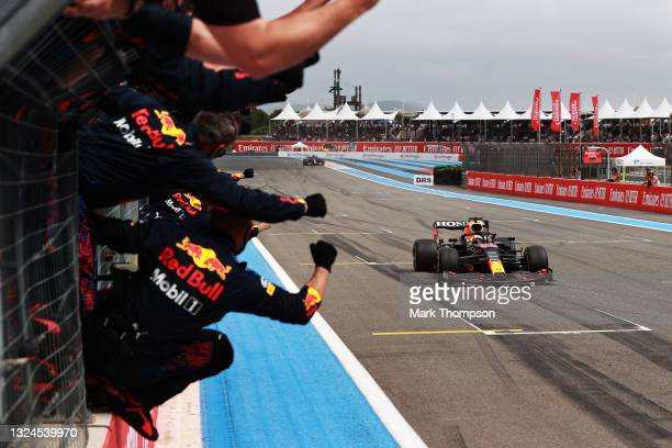 Red Bull Racing team members celebrate on the pitwall as Max Verstappen of the Netherlands driving the Red Bull Racing RB16B Honda crosses the finish...