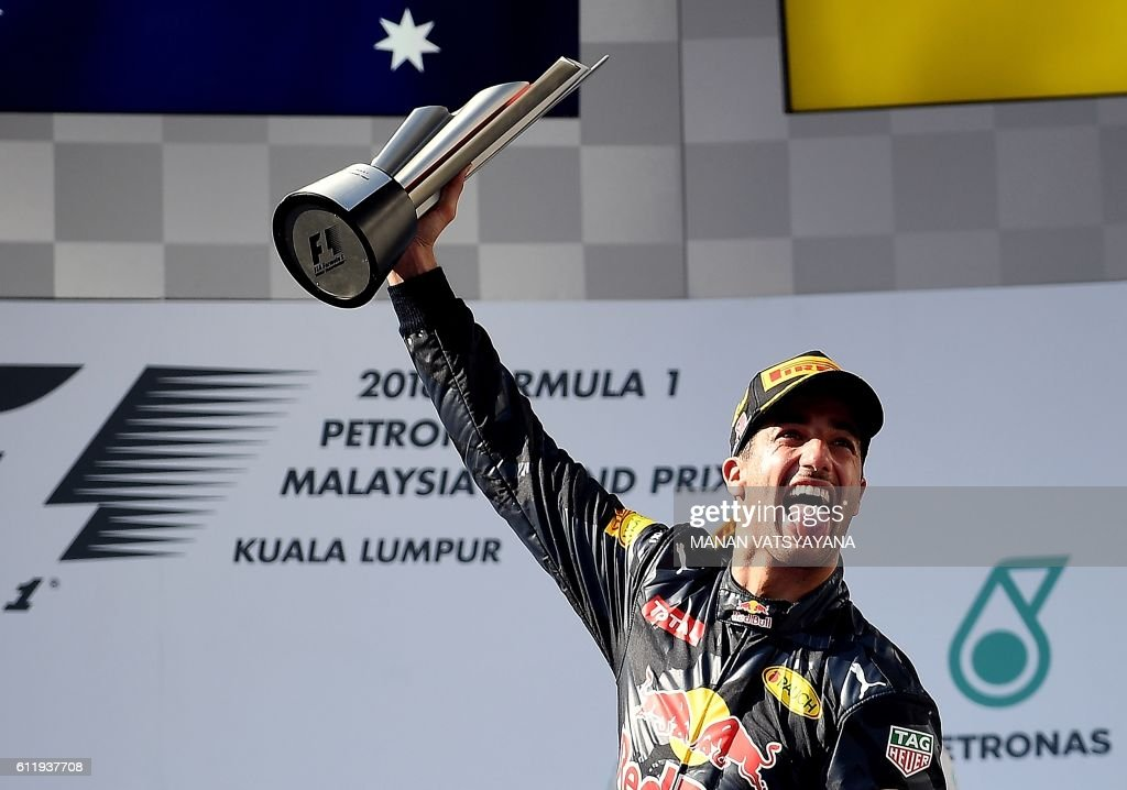 TOPSHOT - Red Bull Racing's Australian driver Daniel Ricciardo celebrates his victory on the podium during the Formula One Malaysian Grand Prix in Sepang on October 2, 2016. /