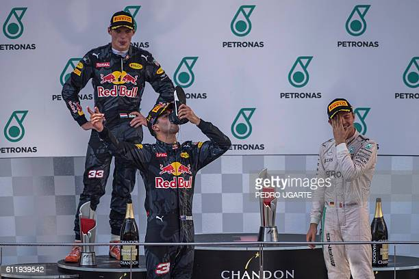 Red Bull Racing's Australian driver Daniel Ricciardo drinks champagne from his shoe as he celebrates his victory on the podium next to second-placed...