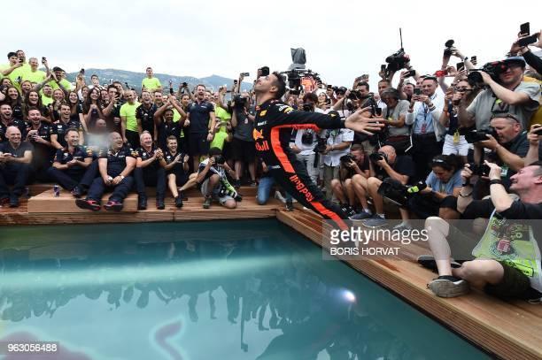TOPSHOT Red Bull Racing's Australian driver Daniel Ricciardo jumps into a pool as he celebrates after winning the Monaco Formula 1 Grand Prix at the...