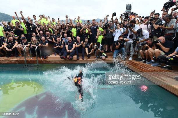 TOPSHOT Red Bull Racing's Australian driver Daniel Ricciardo jumps into a pool as he celebrates after winning the Monaco Formula 1 Grand Prix at the...