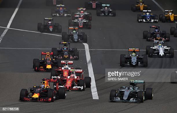 Red Bull Racing's Australian driver Daniel Ricciardo leads Mercedes AMG Petronas F1 Team's German driver Nico Rosberg into the first corner at the...