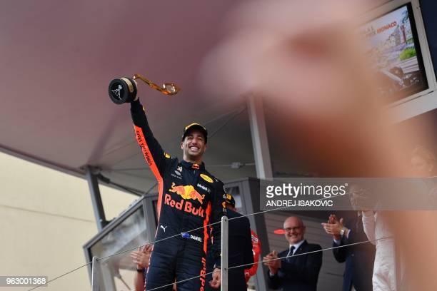 TOPSHOT Red Bull Racing's Australian driver Daniel Ricciardo raises the trophy as he celebrates on the podium after winning the Monaco Formula 1...