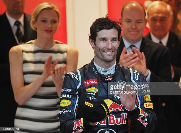 Red Bull Racing's Australian driver Mark Webber celebrates on the podium as Prince albert of Monaco and Princess Charlene stand at the Circuit de...