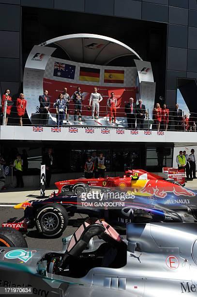 Red Bull Racing's Australian driver Mark Webber Mercedes' German driver Nico Rosberg and Ferrari's Spanish driver Fernando Alonso celebrate on the...