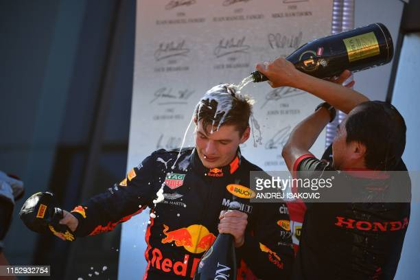 Red Bull Racing's Dutch driver Max Verstappen is soaked in champagne by Toyoharu Tanabe, F1 Technical Director of Honda as he celebrates on the...