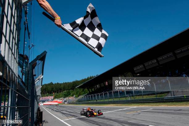 Red Bull Racing's Dutch driver Max Verstappen passes the finish line with the checkered flag during the Austrian Formula One Grand Prix in Spielberg...