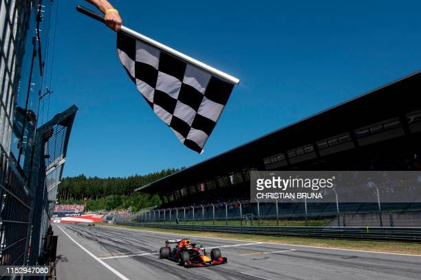 TOPSHOT Red Bull Racing's Dutch driver Max Verstappen passes the finish line with the checkered flag during the Austrian Formula One Grand Prix in...