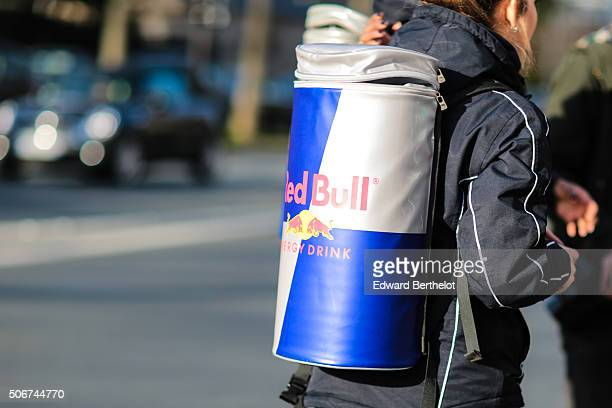 Red Bull representative wearing Red Bull coat and backpack and providing photographers with Red Bull cans after the Dior show during Paris Fashion...
