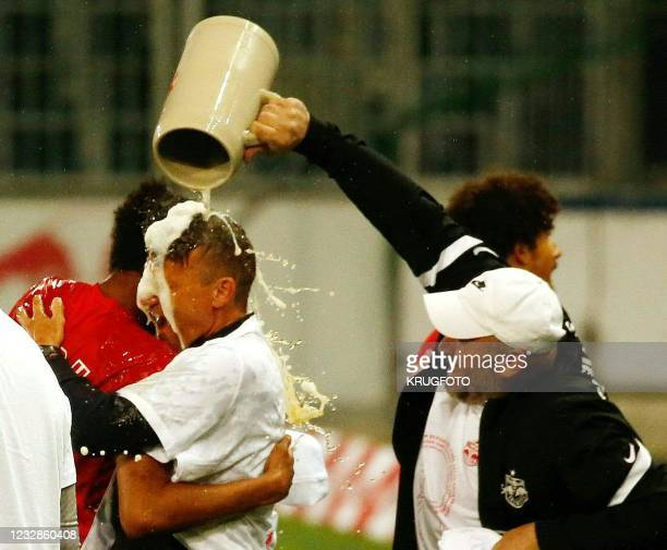 Red Bull Salzburg's head coach Jesse Marsch celebrates and is poured a jug of beer after winning the title after the Austrian Bundesliga football...