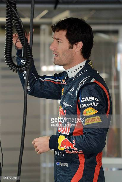Red BullRenault driver Mark Webber of Australia gestures as he gets ready for the first practice session at The Buddh International circuit in...