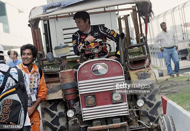 Red Bull-Renault driver Mark Webber of Australia poses in a tractor at the Buddh International circuit in Greater Noida, on the outskirts of New...