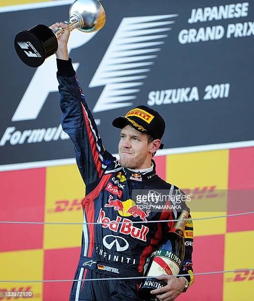 Red BullRenault driver Sebastian Vettel of Germany raises the third place trophy on the podium after coming third in the Formula One Japanese Grand...