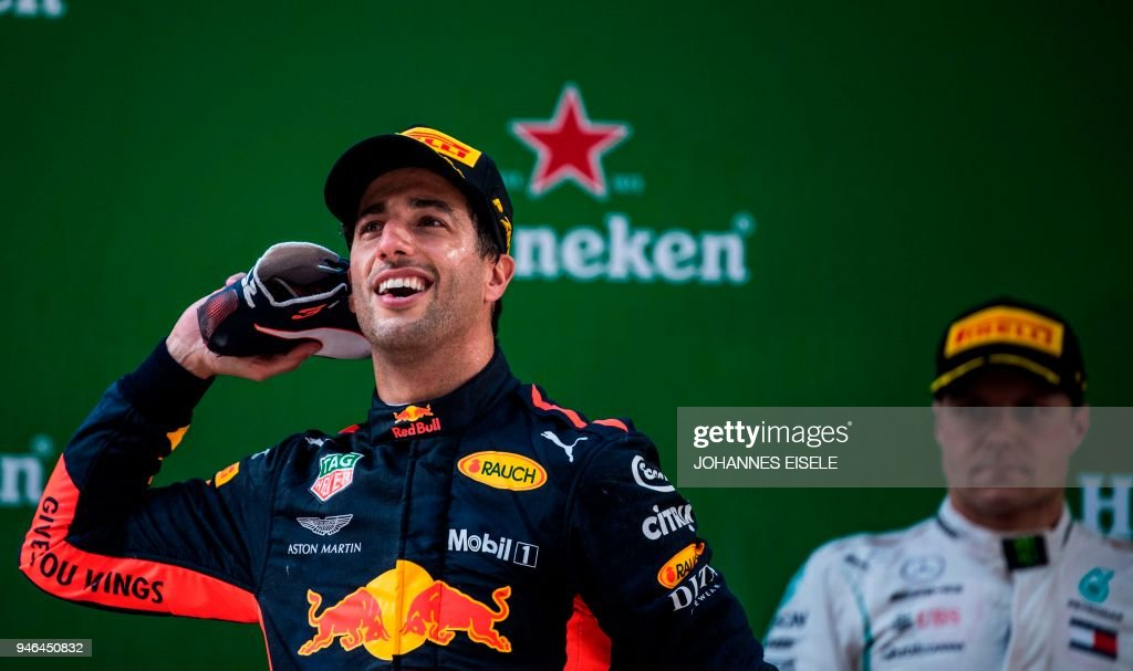 TOPSHOT - Red Bull's Australian driver Daniel Ricciardo celebrates with his shoe on the podium after winning of the Formula One Chinese Grand Prix in Shanghai on April 15, 2018. / AFP PHOTO / Johannes EISELE