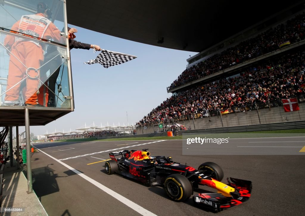 TOPSHOT - Red Bull's Australian driver Daniel Ricciardo crosses the checkered flag to win the Formula One Chinese Grand Prix in Shanghai on April 15, 2018. /