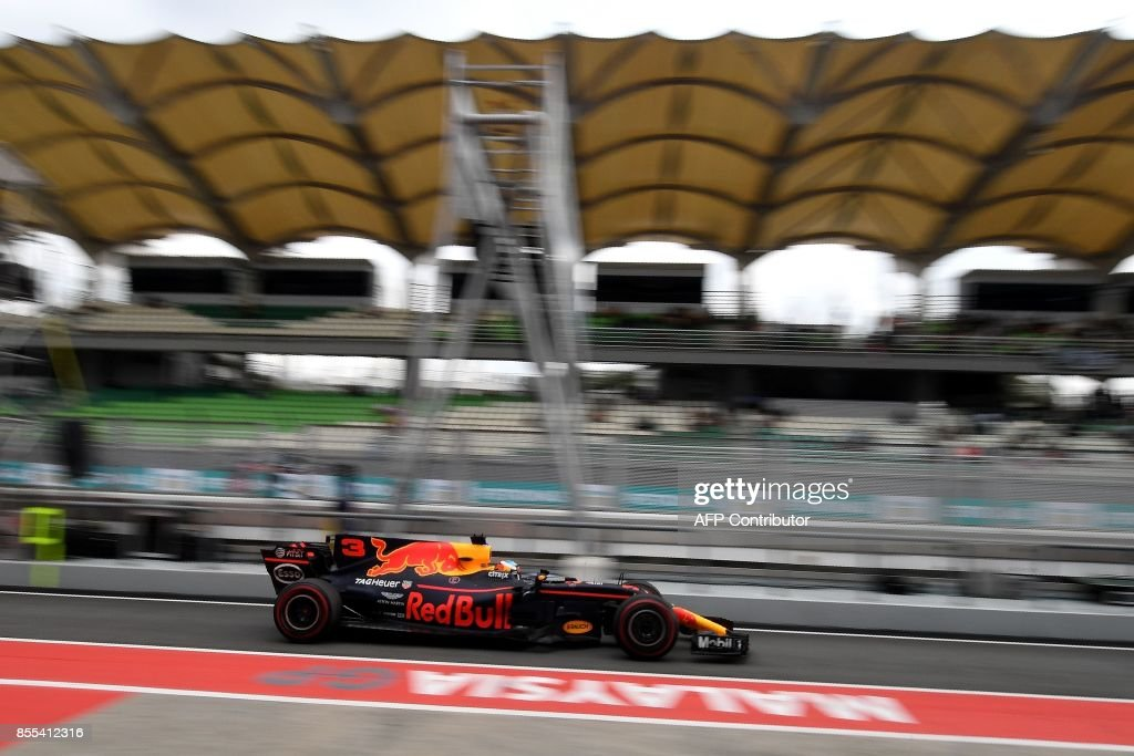 Red Bull's Australian driver Daniel Ricciardo drives in pit-lane during the second practice session of the Formula One Malaysia Grand Prix in Sepang on September 29, 2017. /