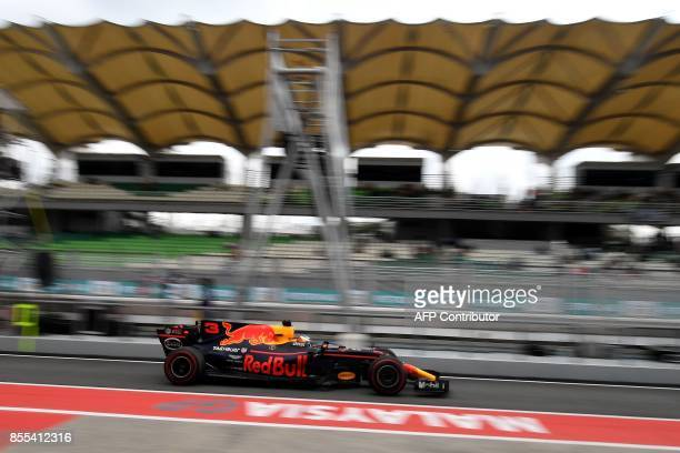 Red Bull's Australian driver Daniel Ricciardo drives in pitlane during the second practice session of the Formula One Malaysia Grand Prix in Sepang...