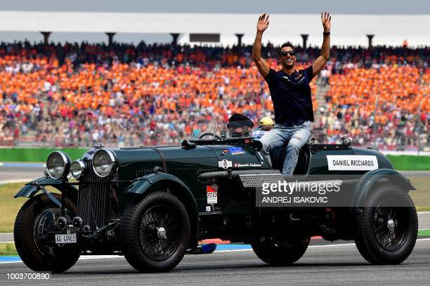 Red Bull's Australian driver Daniel Ricciardo waves during the drivers parade ahead the German Formula One Grand Prix at the Hockenheimring racing...
