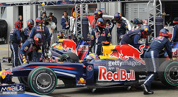 Red Bull's Australian driver Mark Webber and his German team mate Sebastian Vettel stand in their cars in the pits of the Nurburgring racetrack on...