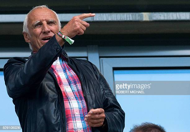 Red Bull's Austrian founder Dietrich Mateschitz gestures from the VIP stands prior tothe German second division Bundesliga football match between RB...