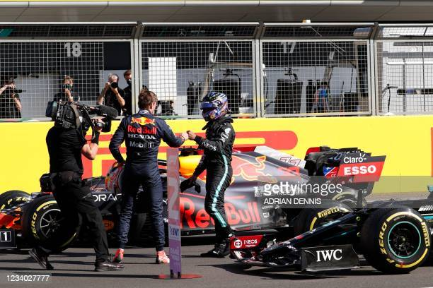 Red Bull's Dutch driver Max Verstappen and Mercedes' British driver Lewis Hamilton bump fists after the sprint session of the Formula One British...