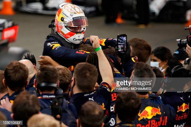 Red Bull's Dutch driver Max Verstappen celebrates with his team after winning the Abu Dhabi Formula One Grand Prix at the Yas Marina Circuit in the...