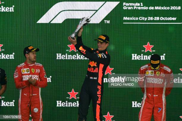Red Bull's Dutch driver Max Verstappen celebrates with his trophy on the podium after winning the F1 Mexico Grand Prix next to runnerup Ferrari's...
