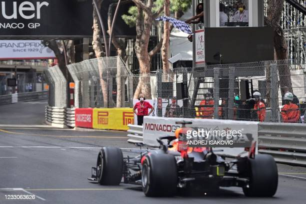 Red Bull's Dutch driver Max Verstappen crosses the finishing line as US tennis player Serena Williams waves the checkered flag during the Monaco...