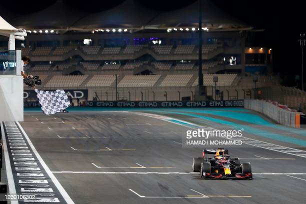 Red Bull's Dutch driver Max Verstappen crosses the line to win the Abu Dhabi Formula One Grand Prix at the Yas Marina Circuit in the Emirati city of...