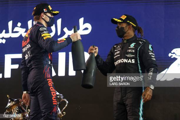 Red Bull's Dutch driver Max Verstappen greets Mercedes' British driver Lewis Hamilton on the podium after the Bahrain Formula One Grand Prix at the...