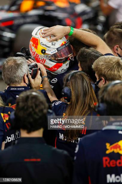 Red Bull's Dutch driver Max Verstappen is cheered by his team after winning the Abu Dhabi Formula One Grand Prix at the Yas Marina Circuit in the...