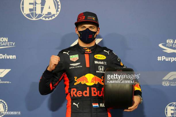 Red Bull's Dutch driver Max Verstappen poses for a picture with the Pole Position trophy after the qualifying session on the eve of the Abu Dhabi...
