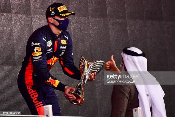 Red Bull's Dutch driver Max Verstappen receives his 1st-place trophy on the podium after the Abu Dhabi Formula One Grand Prix at the Yas Marina...
