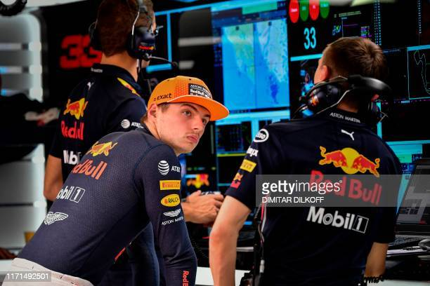 Red Bull's Dutch driver Max Verstappen speaks with a technician in the team's box during the second practice session for the Formula One Russian...