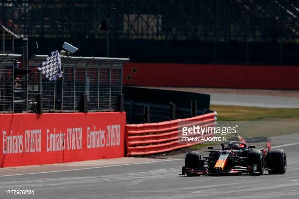 Red Bull's Dutch driver Max Verstappen takes the chequered flag to win the F1 70th Anniversary Grand Prix at Silverstone on August 9, 2020 in...