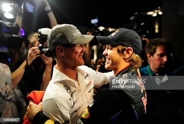 Red Bull's German driver Sebastian Vettel is congratulated by Mercedes GP's German driver Michael Schumacher with his team members at the Yas Marina...