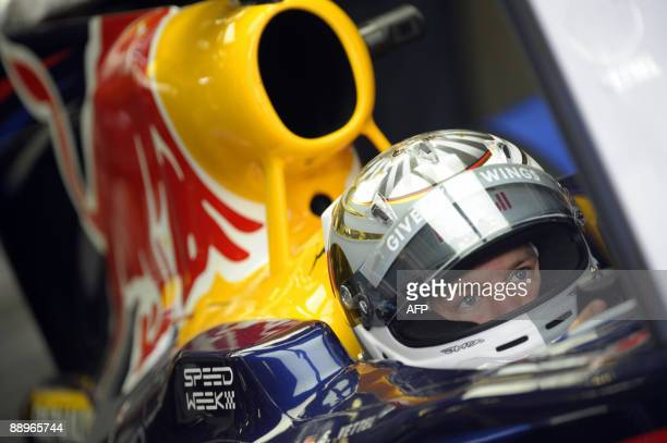 Red Bull's German driver Sebastian Vettel sits in his car in the pits of the Nurburgring racetrack on July 10 2009 in Nurburg during the second free...