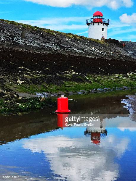 red buoy floating at harbor with lighthouse seen in background against cloudy sky - llanelli stock pictures, royalty-free photos & images