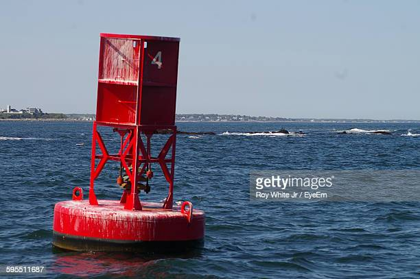 Red Buoy Floating On Sea Against Clear Sky