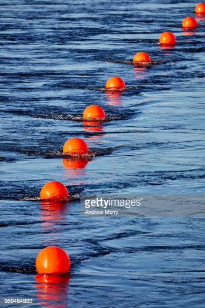 red buoy line, floating barrier in river - buoy stock photos and pictures