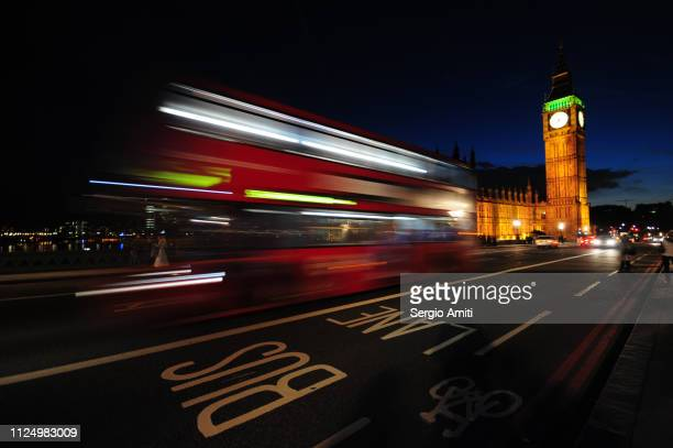 Red bus light trails by Big Ben