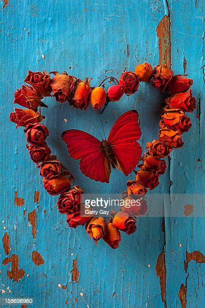 Red butterfly in a dried rose heart wreath