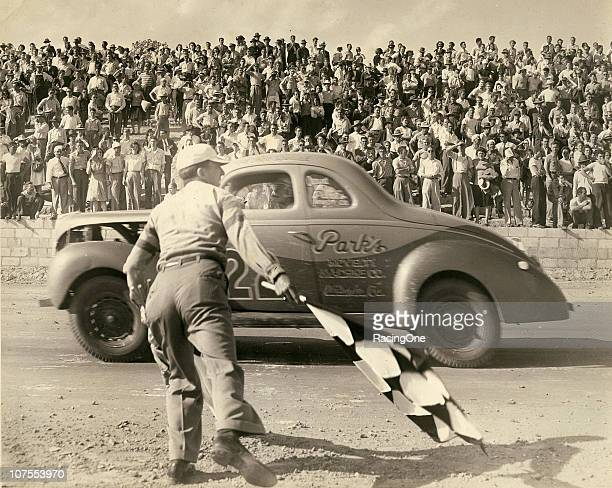 Red Byron takes the checkered flag at the end of a dirt track race somewhere in Georgia during his preNASCAR Modified racing days