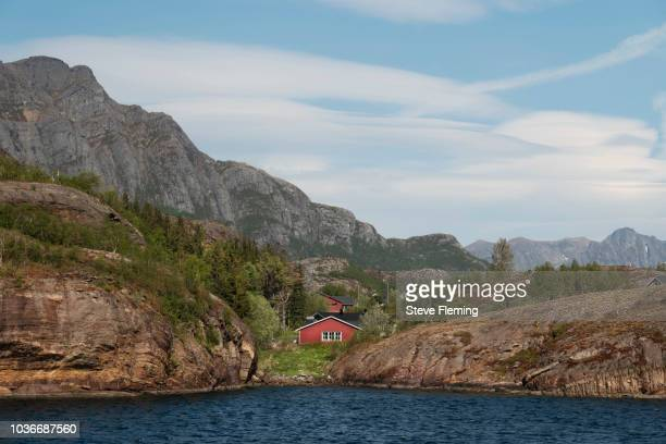 Red cabin on the shores of a fjord, Norway.