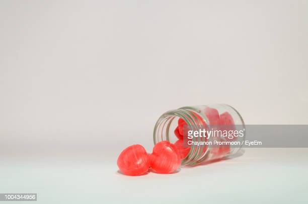 Red Candies In Jar Against White Background