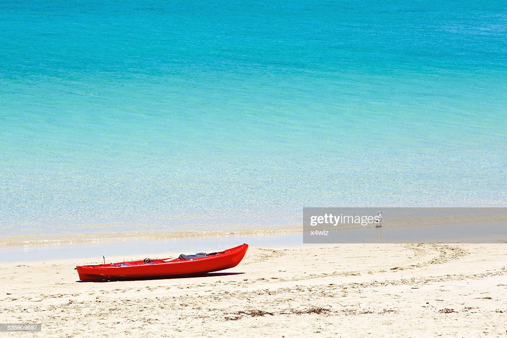 Red canoe on sandy beach : Stock Photo