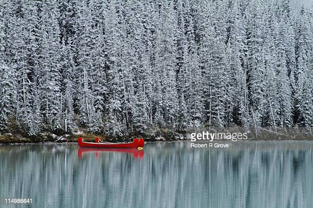 Red canoes and snowed covered pines