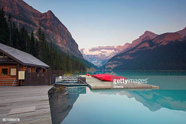 Red canoes at glacial Lake Louise with Victoria glacier Banff National Park Alberta Canada